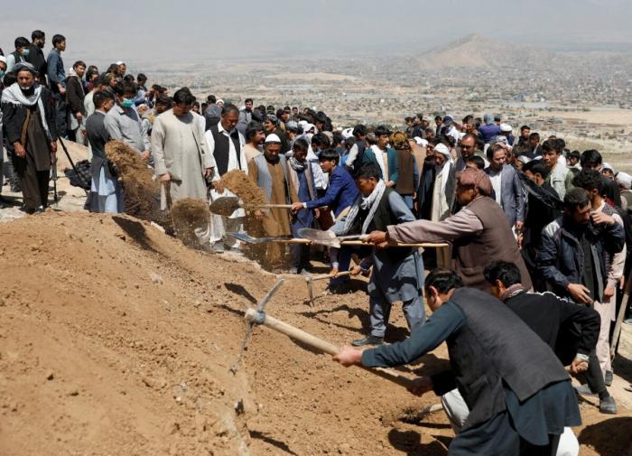 Мужчины копают могилы для жертв теракта в Кабуле. Афганистан, 9 мая 2021 года. Stringer/Reuters