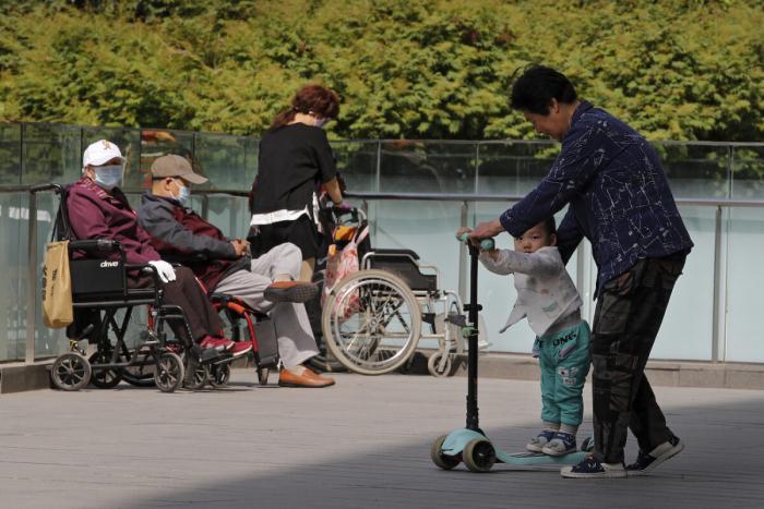 A Женщина играет с ребёнком рядом с пожилыми людьми в инвалидных колясках, отдыхающими на территории коммерческого офисного здания в Пекине 10 мая 2021 года.