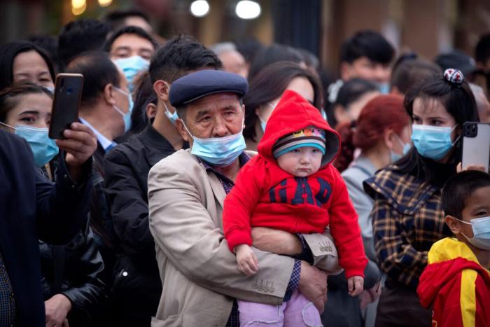 Мужчина держит ребёнка на Гранд базаре в Урумчи, Синьцзян-Уйгурский автономный район, Китай, 21 апреля 2021 г.