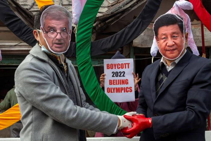 Активисты в масках президента МОК Томаса Баха (слева) и президента Китая Си Цзиньпина позируют перед бутафорными олимпийскими кольцами-виселицами на акции протеста против проведения зимних Олимпийских игр 2022 года в Пекине. Дхармсал, Индия, 3 февраля 2021 г.