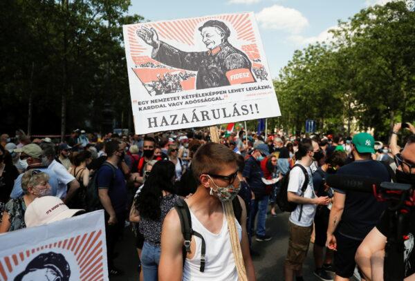 Демонстрант держит плакат с надписью «Измена» во время акции протеста против строительства кампуса Китайского университета Фудань в Будапеште, Венгрия, 5 июня 2021 г.