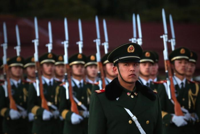 Офицер военизированной полиции стоит на страже во время церемонии спуска флага на площади Тяньаньмэнь в Пекине 13 ноября 2012 г.