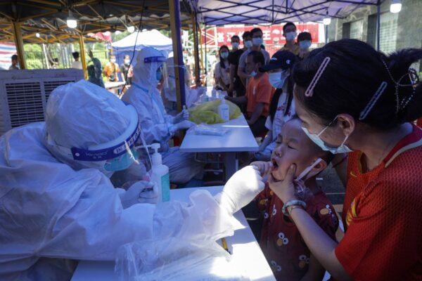 30 мая 2021 года в Гуанчжоу южной китайской провинции Гуандун проводят тестирование ребёнка на COVID-19.