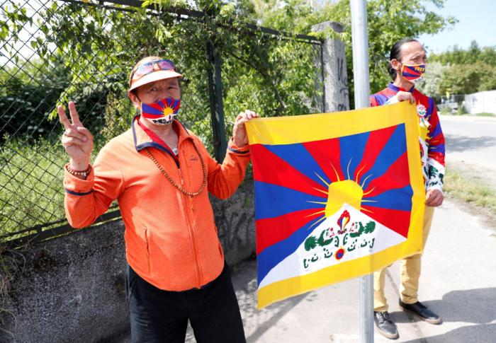 Активисты держат тибетский флаг рядом с дорожным знаком на улице, переименованной в «Мученики Уйгура», недалеко от запланированного места расположения кампуса китайского университета в Будапеште, Венгрия, 2 июня 2021 г.