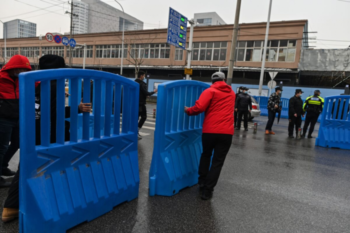 Рабочие устанавливают барьеры за пределами закрытого оптового рынка морепродуктов Хуанань во время визита членов группы ВОЗ, изучающих причины заболевания COVID-19, в Ухане, центральная китайская провинция Хубэй, 31 января 2021 г.