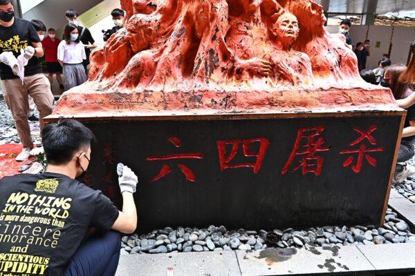 Студент перед «Столпом позора» в Гонконге, 4 июня 2021 года. На основании статуи изображены слова «Резня 4 июня».