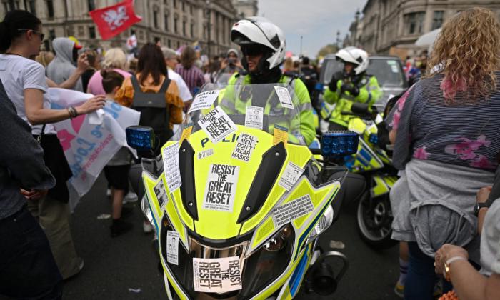 Полицейские мотоциклисты пробираются через марш протеста во время митинга «Вместе за свободу» против паспорта вакцинации и против правительственных ограничений на изоляцию из-за вируса КПК, в центре Лондона 29 мая 2021 года.