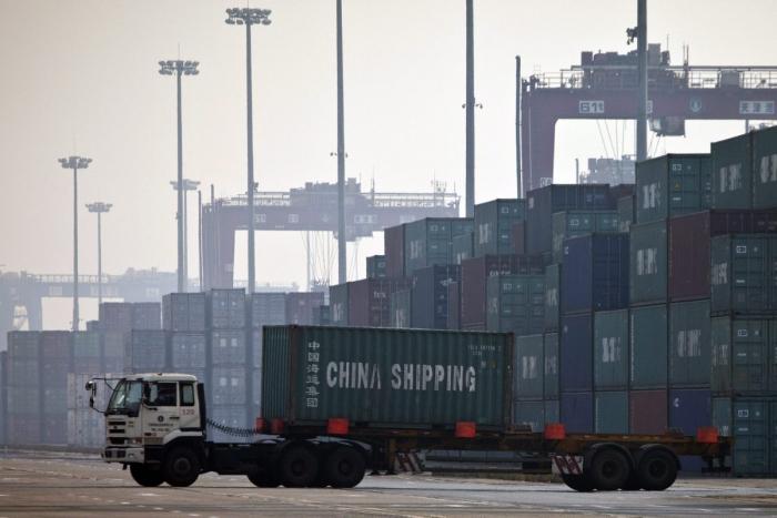 Грузовик перевозит контейнер для погрузки на корабль в порту в Тяньцзине, Китай.