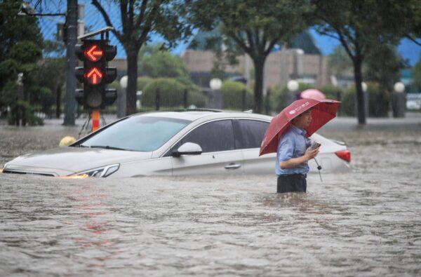 Мужчина идёт по затопленной улице мимо затонувшего автомобиля после проливных дождей в Чжэнчжоу, провинция Хэнань в центральном Китае, 20 июля 2021 года.