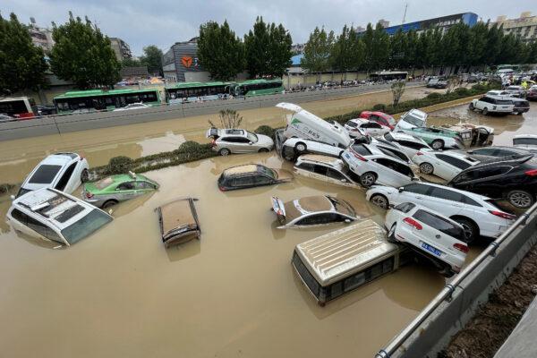 Автомобили стоят в паводковых водах после проливных дождей, обрушившихся на город Чжэнчжоу в провинции Хэнань в центральном Китае 21 июля 2021 г.