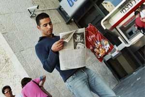 Иерусалим, Израиль: Прохожий читает эксклюзивный выпуск газеты *The Epoch Times* *Девять комментариев о коммунистической партии*, полученный от участников митинга *Мир без коммунизма* 11 ноября 2005 г. Фото: Юлия Гросс/The Epoch Times