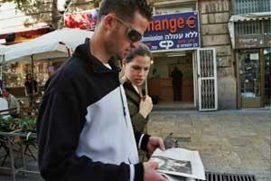 Иерусалим, Израиль: Молодая семья читает эксклюзивный выпуск газеты *The Epoch Times* *Девять комментариев о коммунистической партии*, полученный от участников митинга *Мир без коммунизма* 11 ноября 2005 г. Фото: Юлия Гросс/The Epoch Times